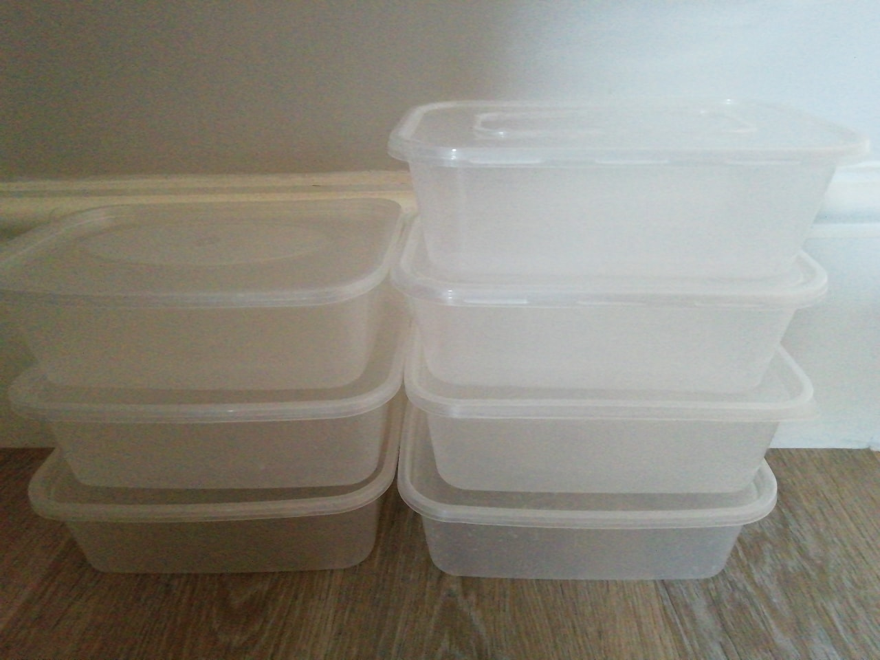 7 reusable takeaway plastic containers with lids.